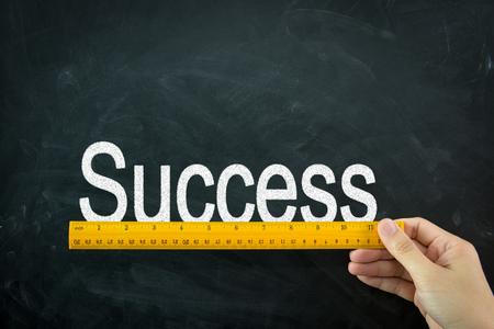 Yellow wooden ruler measures the word success on blackboard Stock fotó