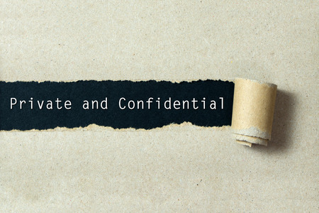 torn paper background: Private and confidential written on torn paper black background