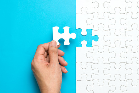 Hand put the last piece of jigsaw puzzle to complete the mission Standard-Bild