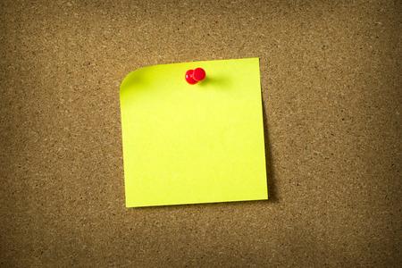 cork sheet: Blank yellow sticky note pinned on corkboard
