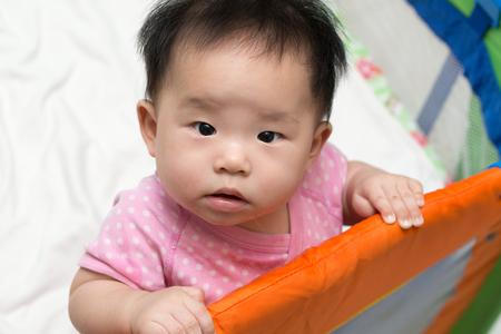 bedtime: Portrait of an asian baby in playpen