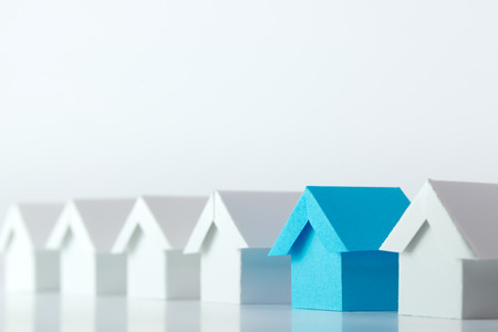 Blue house in among white houses for real estate property industry Stockfoto