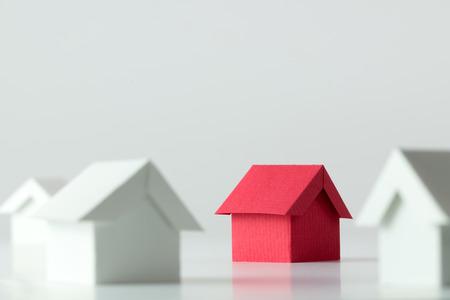 Maison rouge au milieu des maisons blanches pour l'industrie des biens immobiliers Banque d'images