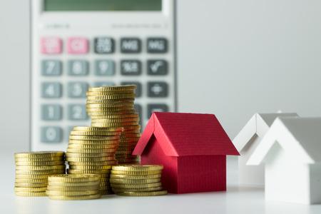 calculadora: casa, monedas de oro y una calculadora de préstamo de hipoteca conceptual