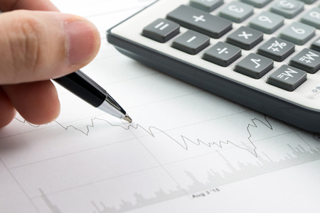 Stock market analysis with calculator and pen