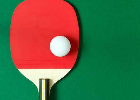 tabletennis: paddle with a white ball on green table