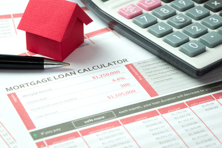 ed: Mortgage loan balance sheet with a miniature ed paper house and calculator Stock Photo