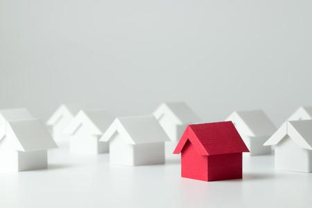 Rood huis in onder witte huizen voor onroerend goed-industrie