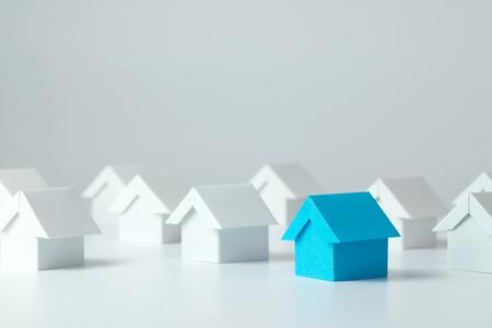 Maison bleue au milieu des maisons blanches pour l'industrie des biens immobiliers