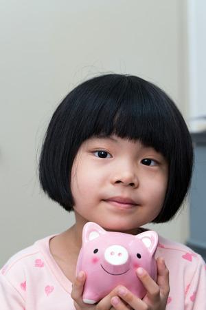 coinbank: Asian child hold a pink piggy bank smiling