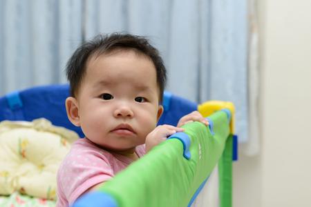 asia children: Portrait of an asian baby in playpen