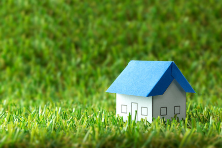 real estate industry: Miniature house model on green field for real estate industry