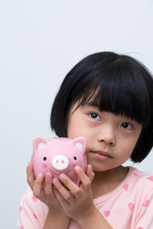 coinbank: Asian child hold a pink piggy bank thinking Stock Photo