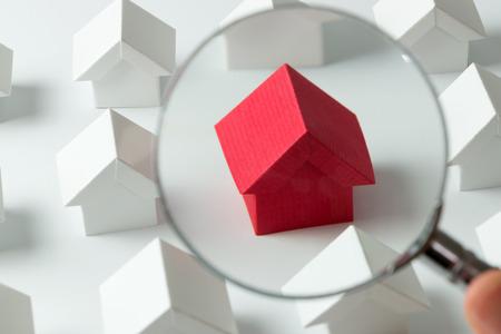 Huis zoeken concept met een vergrootglas Stockfoto