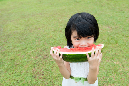 Asian child eating watermelon in the park photo