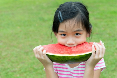 eating fruits: Asian child eating watermelon in the park