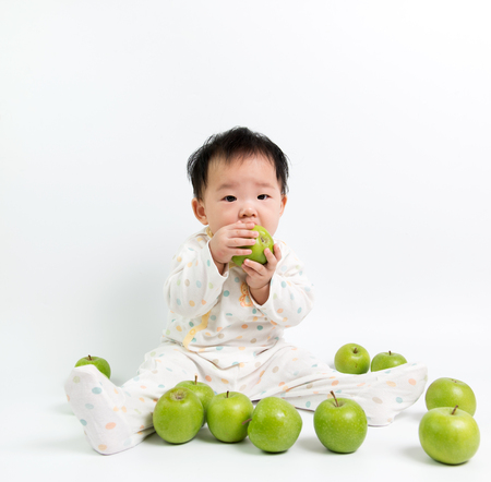 흰색 배경에 녹색 사과 먹는 아시아 아기