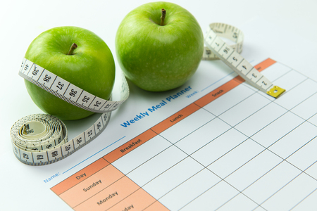 Weekly meal planner with green apples and tape measurement Foto de archivo
