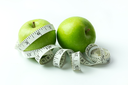 tailors tape: Green apple wrapped in a tailors tape measure Stock Photo