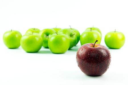 manzana roja: manzana roja, destacándose entre las manzanas verdes sobre fondo blanco Foto de archivo