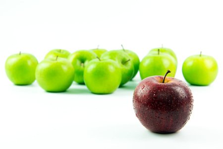 standing out: Red apple standing out among the green apples over white background