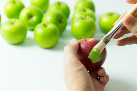 assimilate: Concept of assimilation by painting red apple into green color