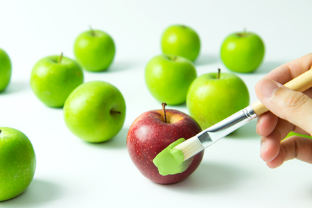 assimilation: Concept of assimilation by painting red apple into green color