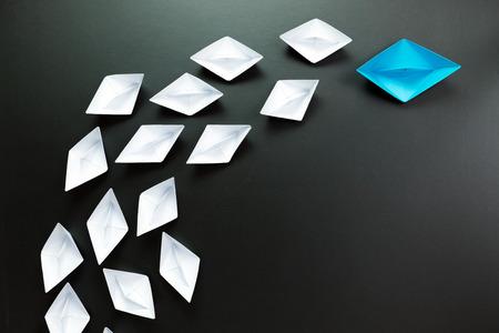 supervisión: Concepto de la dirección con la nave azul líder entre el blanco Foto de archivo