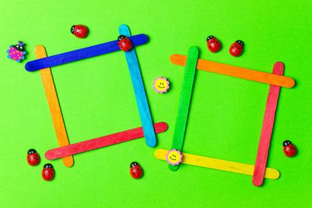 photos of pattern: Ice cream sticks photos frames over green background