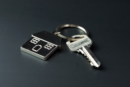 keychain: Keys on metal house figure keychain over black background Stock Photo