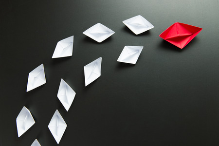 Leadership concept with red ship leading among the white Stockfoto