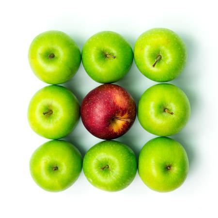 흰색 배경 위에 녹색 사과 가운데 서 빨간 사과