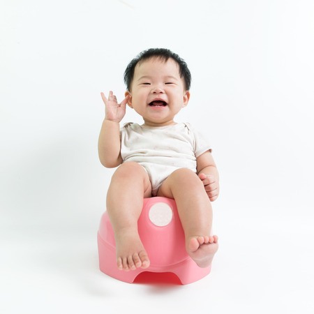 Asian baby sitting on potty over white background