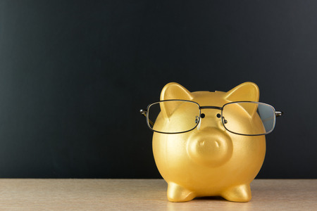 Golden piggy bank wearing glasses with copy space
