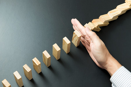 Solution concept with hand stopping wooden blocks from falling in the line of domino Foto de archivo
