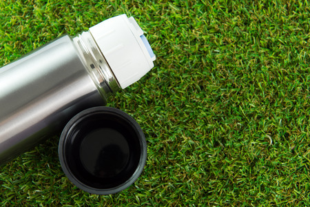 Close up of thermos flask on green grass