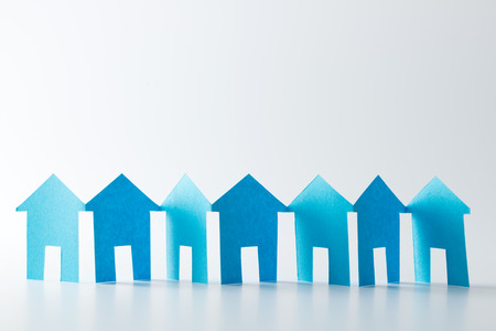 Blaues Papier Häuser in einer Reihe auf weißem Hintergrund