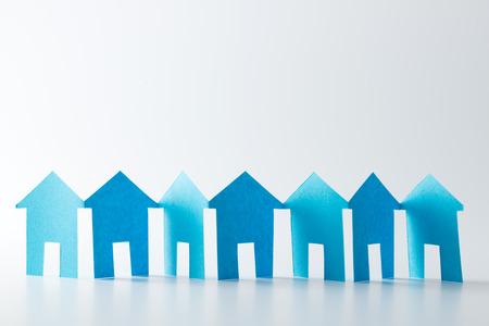 casas de papel azul en una fila en el fondo blanco