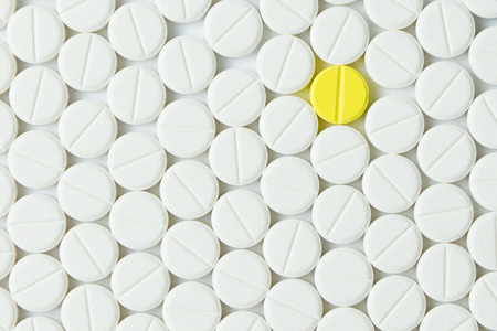 Yellow tablet among the white forming background