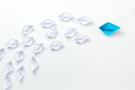 Leadership concept with blue ship leading among the white