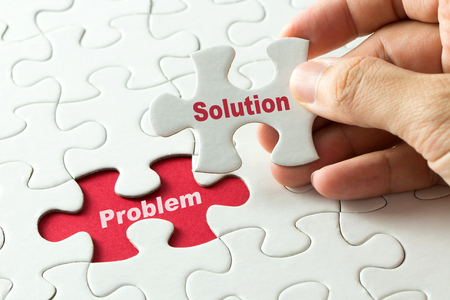Mano que pone la última pieza del rompecabezas con la solución de la palabra para solucionar el problema