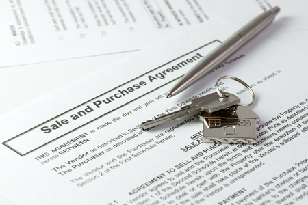 selling house: Ball pen and house key on sale and purchase agreement Stock Photo