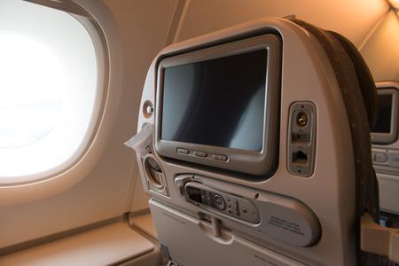 onboard: Window seat inside airplane with blank TV screen