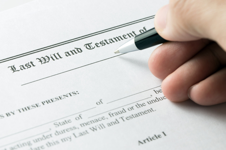 Hand holding pen on last will and testament document Stock Photo