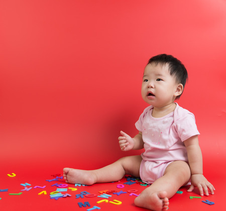 baby toys: Asian baby with wooden alphabets over orange background Stock Photo