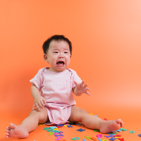 baby toys: Asian baby crying with wooden alphabets on the floor