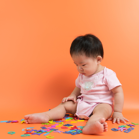 looking at baby: Asian baby looking at the wooden alphabets over orange background