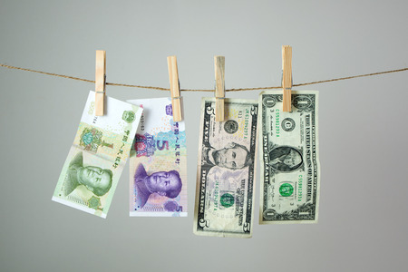 US dollar and China Yuan banknotes hanging on rope for money laundering concept