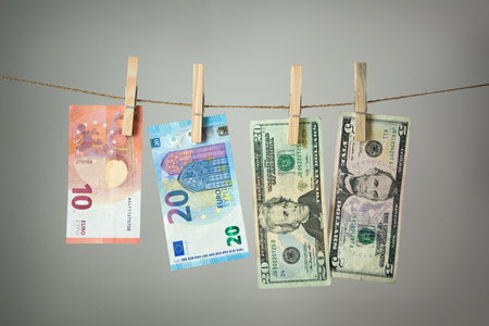 Euro and US banknotes hanging on rope for money laundering conept