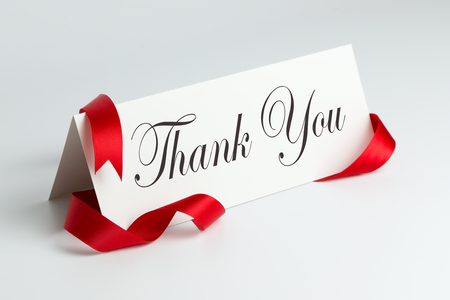 Thank you note with red ribbon over white background Stock Photo